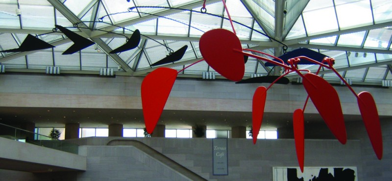 An image of a calder mobile is shown. It has several black and red geometric shapes hanging down.
