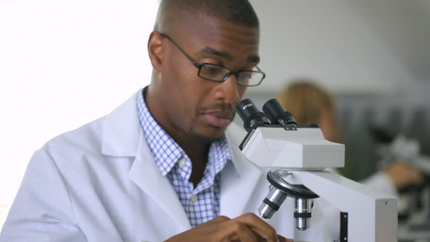 biologist looking at microscope