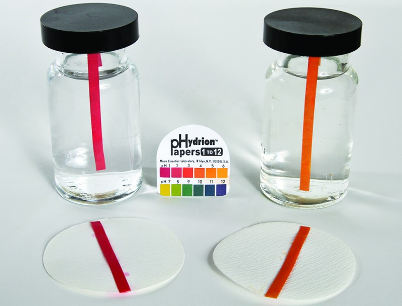This image shows two bottles containing clear colorless solutions. Each bottle contains a single p H indicator strip. The strip in the bottle on the left is red, and a similar red strip is placed on a filter paper circle in front of the bottle on surface on which the bottles are resting. Similarly, the second bottle on the right contains and orange strip and an orange strip is placed in front of it on a filter paper circle. Between the two bottles is a pack of p Hydrion papers with a p H color scale on its cover.