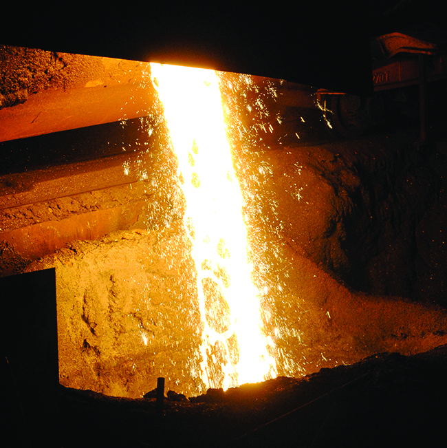 This figure shows a photo of molten iron. A bright yellow-orange glow appears just left of center in the figure. Smoke appears to be rising toward the top center of the figure. Just below and to the right, sparks appear to be falling.