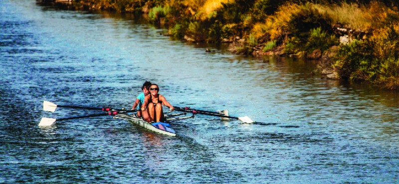 This is a photo of two people rowing a boat in a canal.