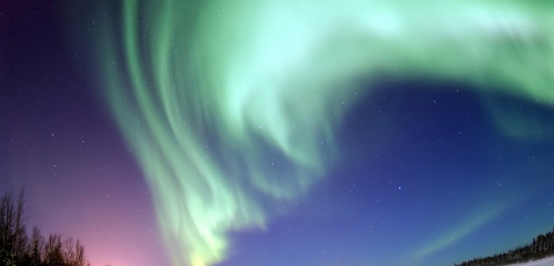 A shimmering curtain of green lights in the sky above a snow covered landscape. Stars are visible in the dusky sky beyond the lights.
