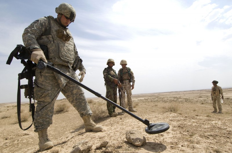 ]Photograph of several soldiers in an open field. One soldier is searching for explosives by scanning the surface using a metal detector.