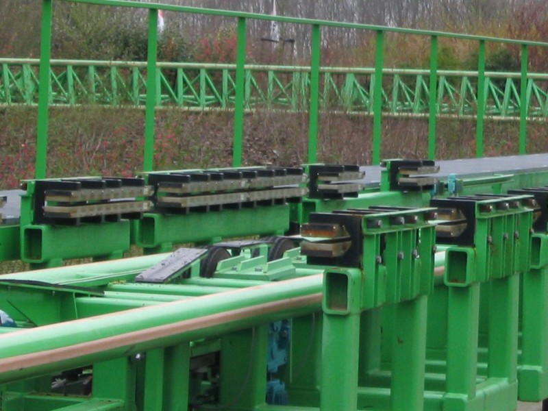 Photograph of a roller coaster track with rows of magnets protruding horizontally that are used for magnetic braking in roller coasters.