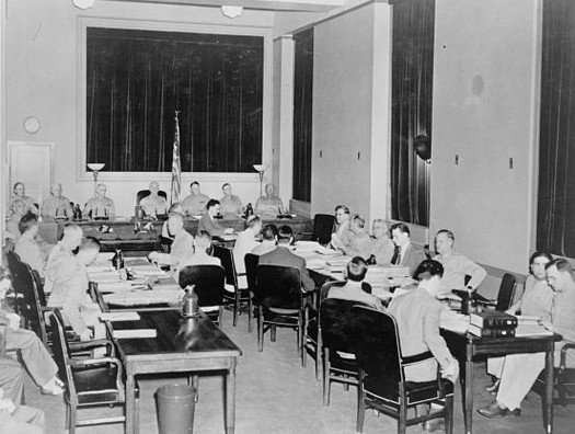 A photo of a group of people in a military commission, seated in chairs around a number of tables arranged in a U shape.