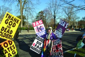A photo of people holding signs. The signs have messages like Thank God for Dead Soldiers and Soldiers Die for Fag Marriage.