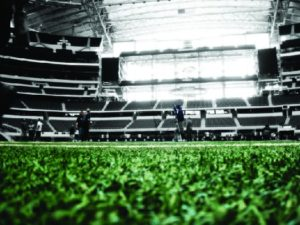 A photo of the inside of a football stadium, showing the field in the foreground and rows of empty seats in the background.
