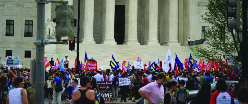 An image of a group of people at the steps of the Supreme Court building. Many people are holding flags marked with the symbol of an equals sign.