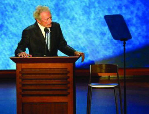 An image of Clint Eastwood standing behind a podium. Next to him on the right is an empty chair.