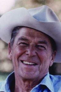 A photo of Ronald Reagan wearing a cowboy hat and denim shirt.